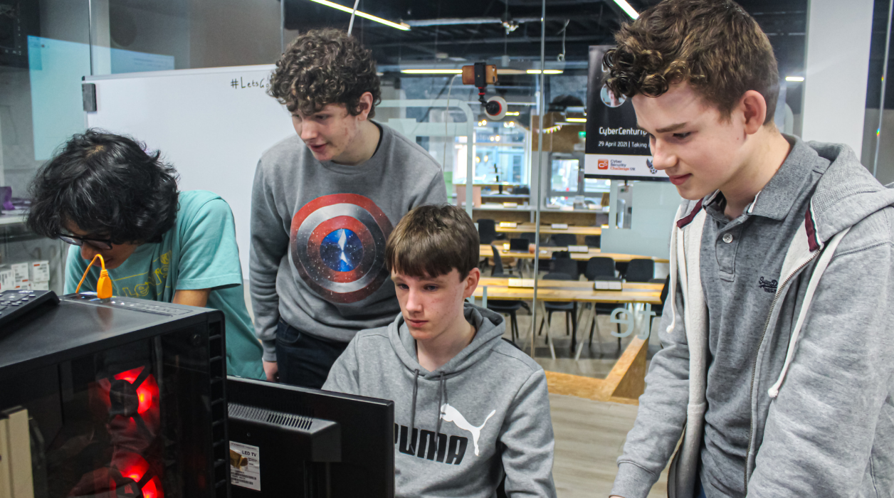 Four boys gathered around a computer in a collaborative working space